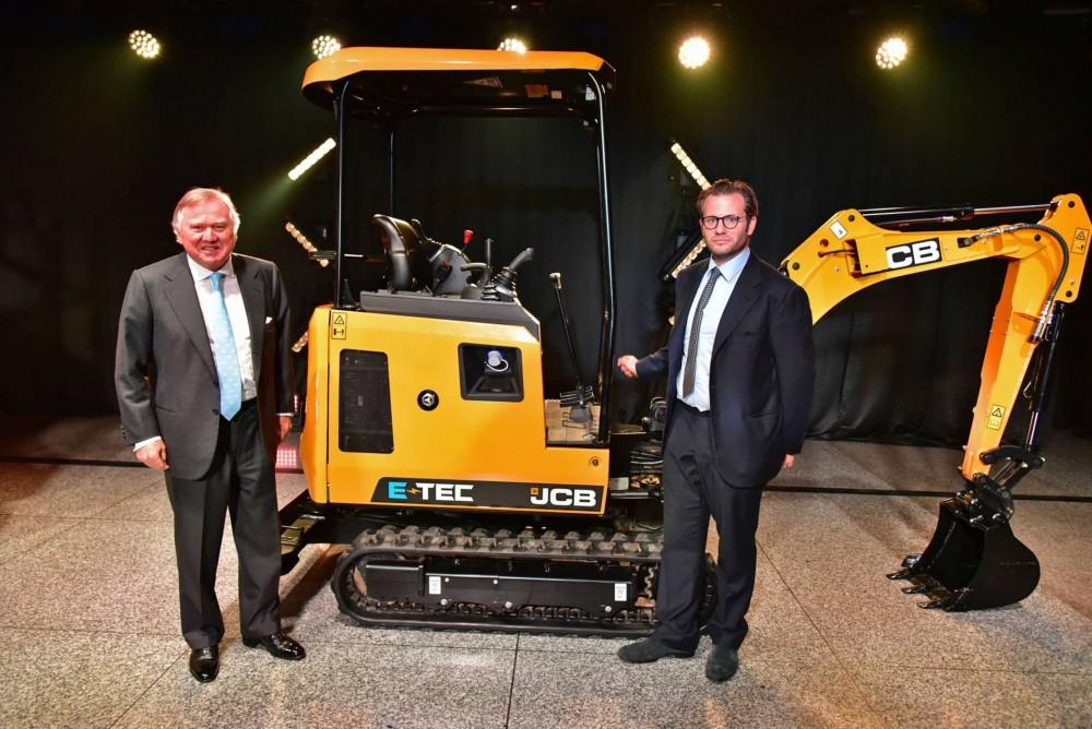 Lord Bamford präsentiert gemeinsam mit seinem Sohn Georg den weltweit ersten Elektrobagger von JCB: den 19C-1 E-TEC