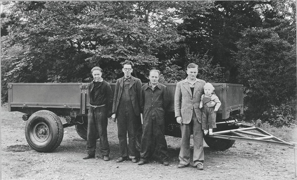 1947 - Anthony Bamford in his father's arm. From left are employees Bill Hirst, Arthur Harrison and Bert Holmes (1920).jpg