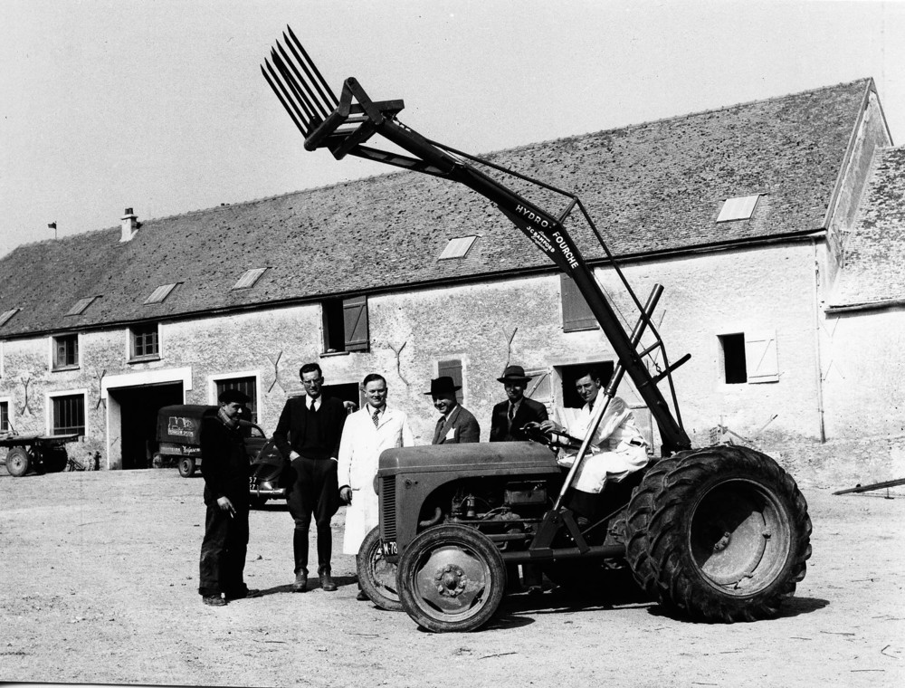1953 - Mr JCB (third from left) with employee Doug Hollingworth (seted) and customers in France (1920).jpg